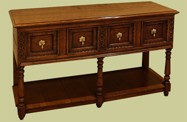 Oak low pot board dresser with carved drawers and legs.