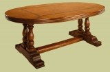 Oak oval dining table on hand carved paired pedestal bases