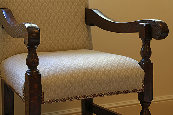Detail of period style upholstered oak armchairs.
