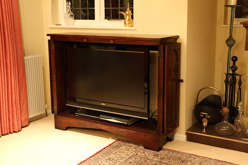 TV cabinet with medieval tracery style doors open, showing flat screen television