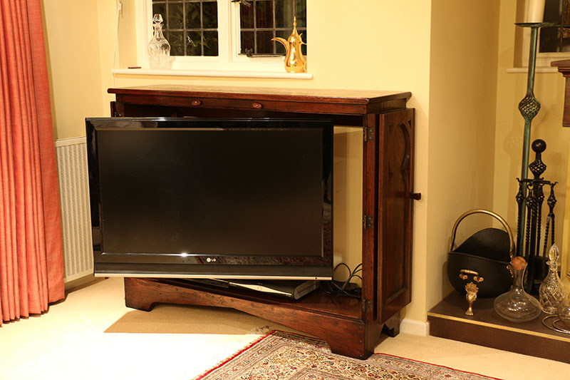 Medieval tracery style TV cabinet with television extended and swiveled for comfortable viewing