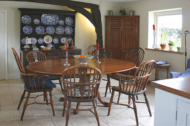 Bespoke oval table to suit clients collection of antique country chairs