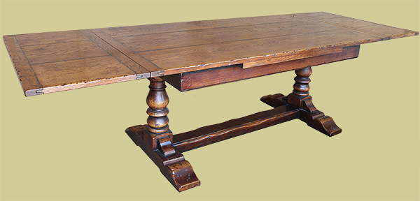 Heavy oak drawerleaf pedestal dining table, in period style, shown here in extended format.