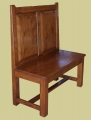 Simple oak hall settle with straight fielded panel back.