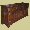 Early oak style closed dresser base, with three fielded panel doors and three drawers.
