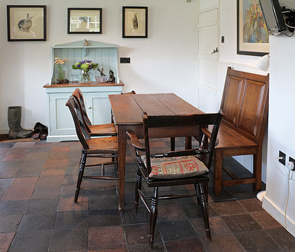 Simple raked back oak panelled settle in dining room of a village cottage.