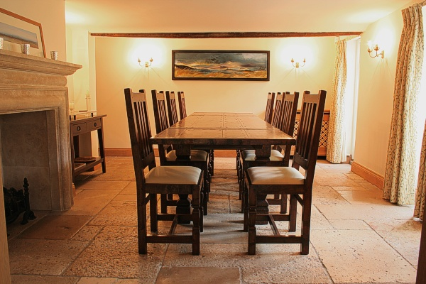 Arts and Crafts style oak extended dining table and upholstered side chairs.