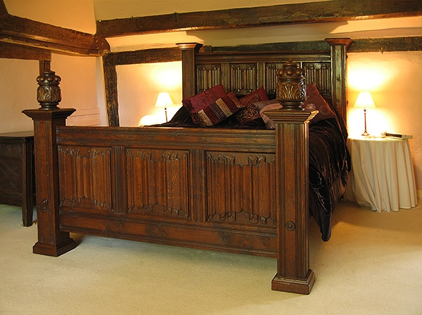 Hand carved oak linenfold bed in timber framed house