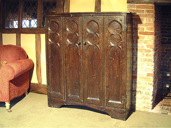 Medieval style oak aumbry for flat screen TV.