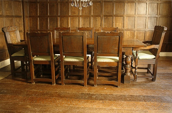 Carved oak dining table and chairs in Tudor panelled room