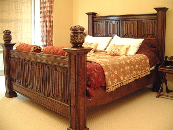 Carved oak bed with linenfold panels to headboard and footboard.