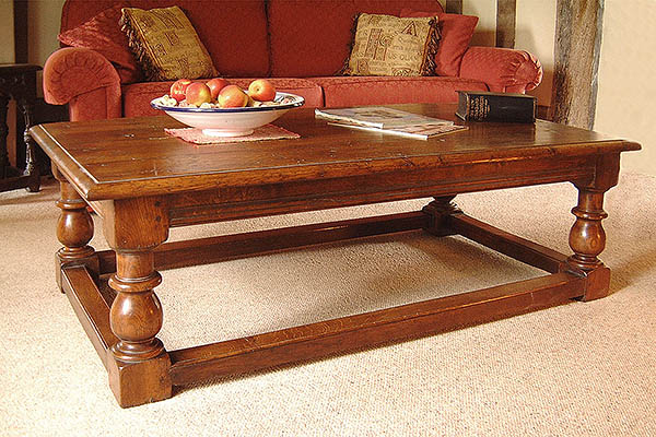 Traditional style baluster leg oak coffee table in period room setting.