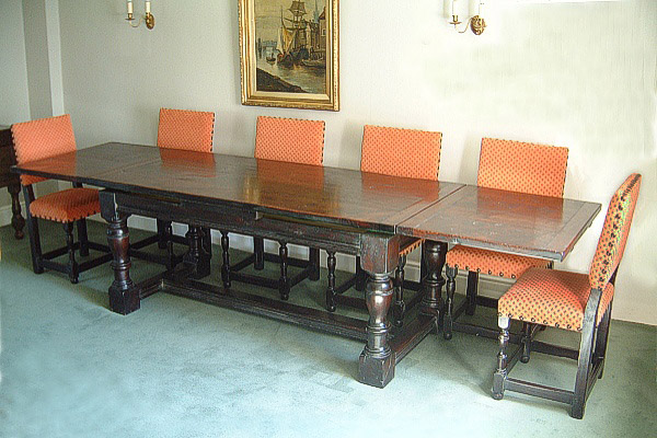 17th century style oak drawerleaf, or withdrawing, table and matching upholstered side chairs.