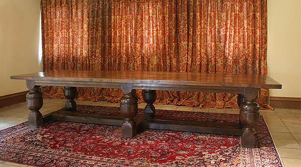 Bulbous 6 leg oak dining table in converted Suffolk barn.
