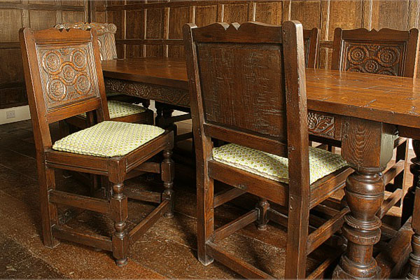 Hand carved Westmorland style oak side chairs in Tudor panelled dining room.