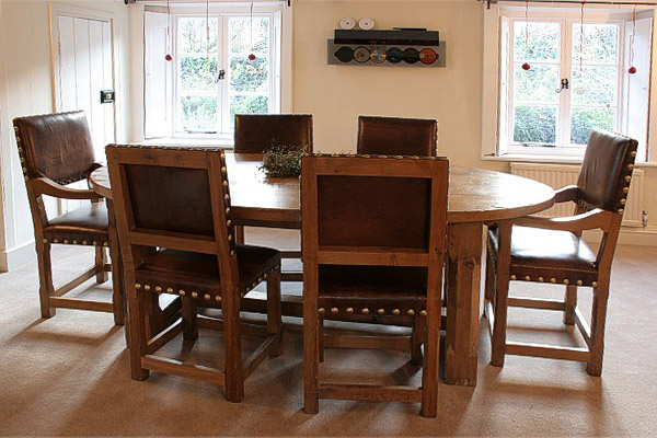 Oak oval top dining table, with stop chamfered legs, photographed with matching leather covered chairs, in our clients West Sussex home.