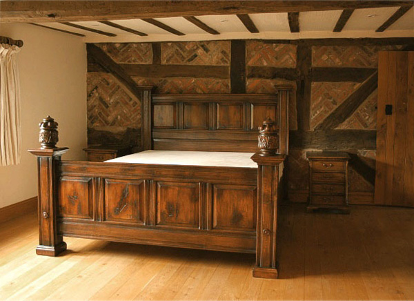 Fielded panel oak bed, with carved finials, in oak beamed house.