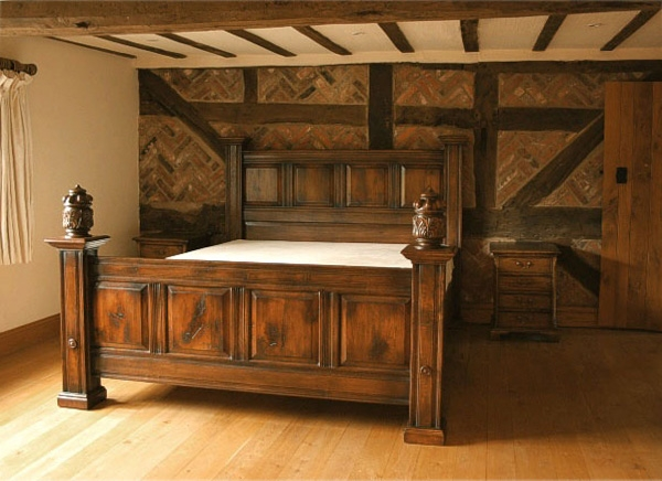 Panelled oak bed in beamed bedroom of old farmhouse