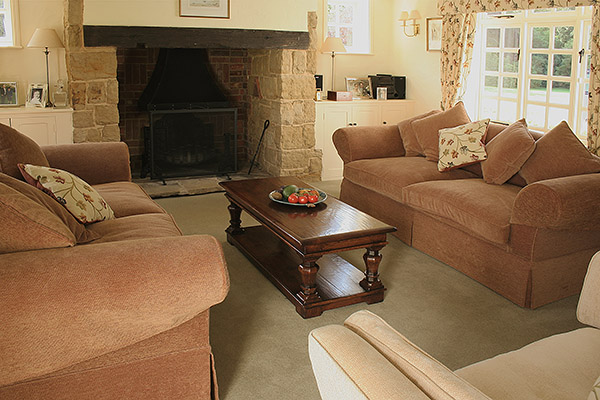 Bespoke oak coffee table with octagonal cut baluster legs, in sitting room of period farmhouse.