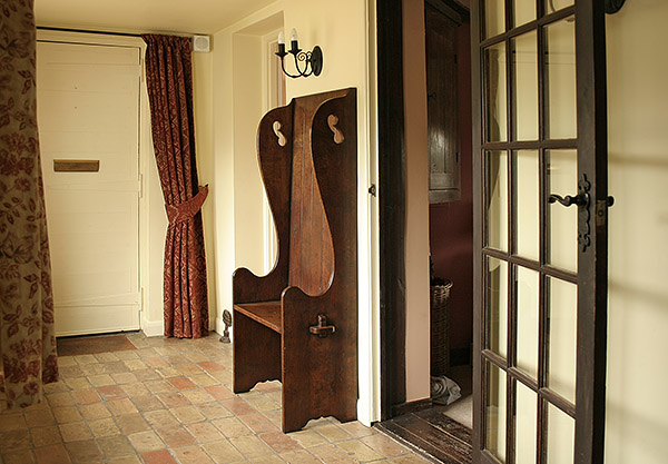 Small oak 18th/19th century period style settle, in hallway of Suffolk cottage.