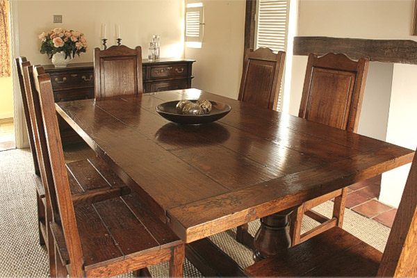 Oak dining table and solid seat chairs, plus period style dresser base in Suffolk cottage.