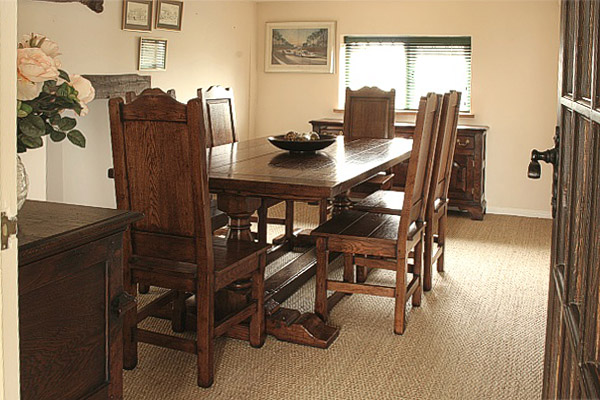 Bespoke oak pedestal table, solid seat side chairs and dresser bases, in dining room of Suffolk country cottage.