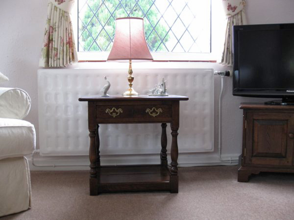 Reproduction oak side table in traditionally styled sitting room