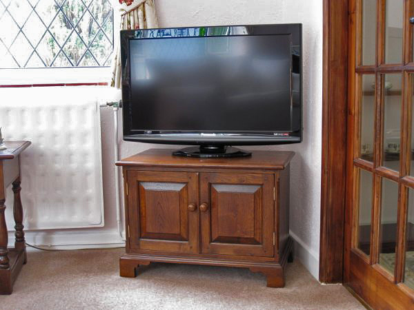 Reproduction oak TV stand, with storage, in a traditionally styled sitting room.