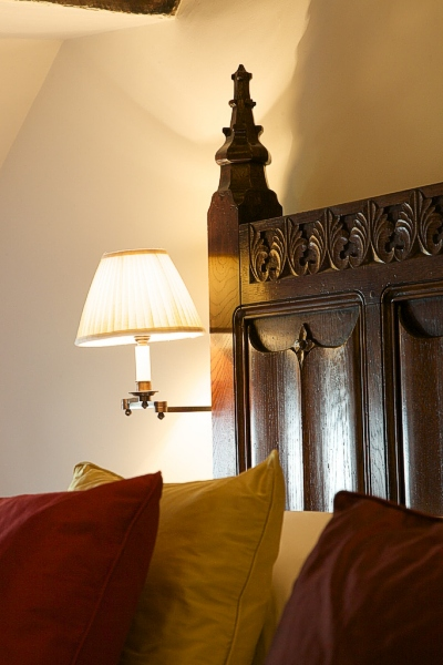 Detail photo of our bespoke 16th century style parchemin panelled bed, in the oak beamed bedroom of our clients Devon longhouse.