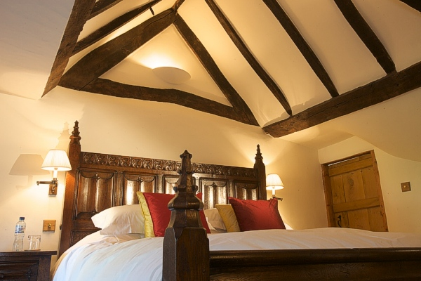 Tudor style oak carved bed in oak beamed bedroom of Devon longhouse.