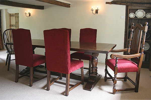 Oak pedestal dining table and upholstered side chairs and armchair, in Sussex thatched cottage.