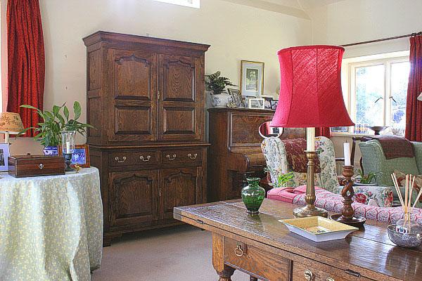 Oak panelled storage cupboard in sitting room of Surrey cottage.