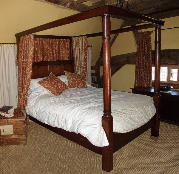 18th century style oak 4-poster bed in heavily beamed room