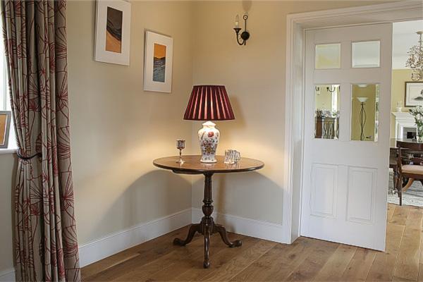 Round oak pedestal lamp table in hallway of converted barn in Warwickshire.