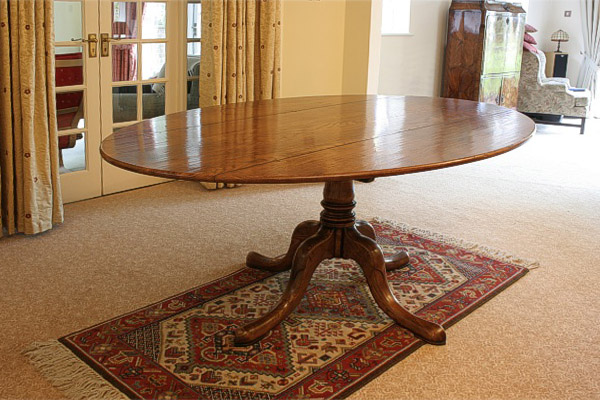 An oval oak dining table, in a pedestal base, in our clients Sussex home.