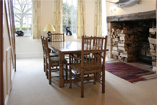 Oak refectory table and spindleback chairs in dining room of Norfolk country house.