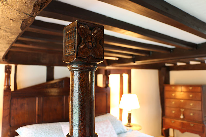 Carved oak foot posts of Tudor style pencil bed