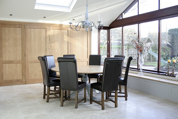 Oak and hand painted traditional style pedestal table, in conservatory style dining room extension.