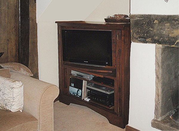 Gothic style oak TV cabinet in sitting room of small cottage