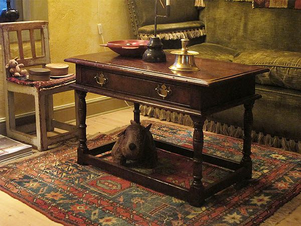 Antique style oak coffee table with drawer, in period house.