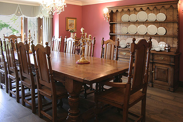 Period style oak furniture, comprising refectory table, side chairs, armchairs and closed dresser with plate rack, in Sussex dining room.