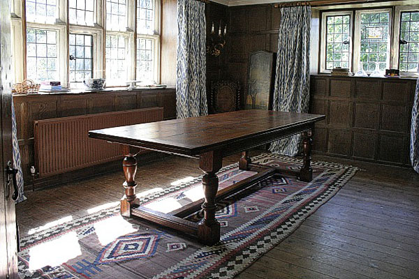 Extending oak dining table, of period design, in historic panelled room.