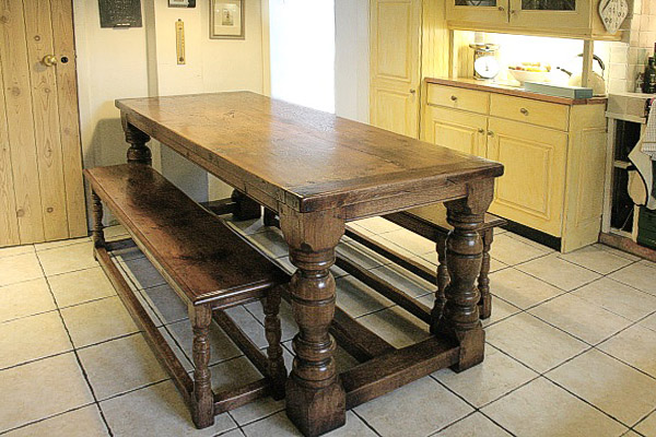 Heavy oak period style dining table and matching benches, in the country kitchen of a Surrey cottage.