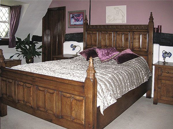 Tudor style oak carved bed and bedside cupboards in 17th century timber framed cottage.