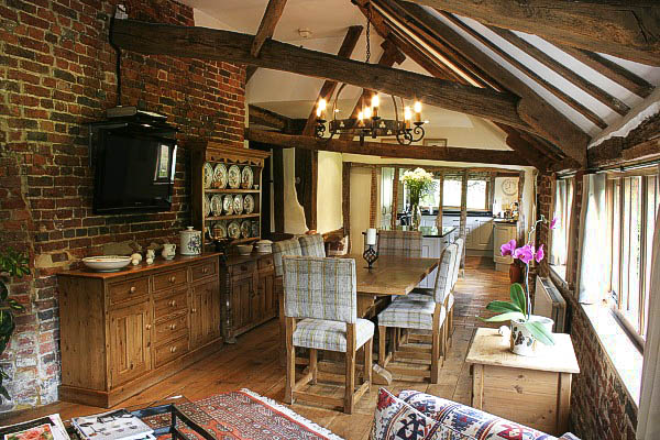 Upholstered oak side chairs and Medieval style oak trestle table in timber framed kitchen.