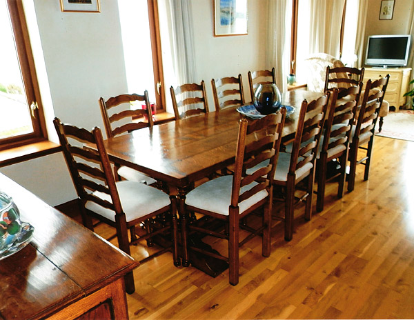 Ladderback leather upholstered dining chairs and twin pedestal table, in Scottish home.
