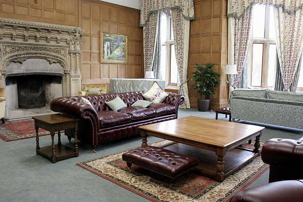 Large square oak potboard coffee table and small oak lamp table in the oak panelled lounge of a converted priory.
