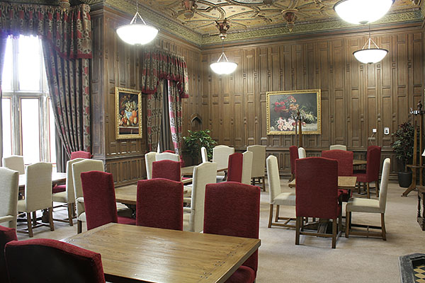 Upholstered chairs in oak panelled dining room of an old converted priory.