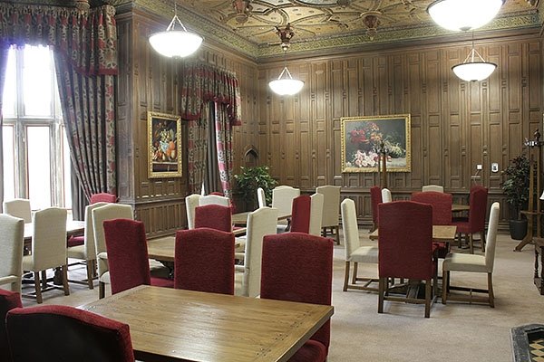 Upholstered side chairs in oak panelled priory dining room