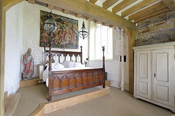 Unique carved oak bed in converted chapel of manor house